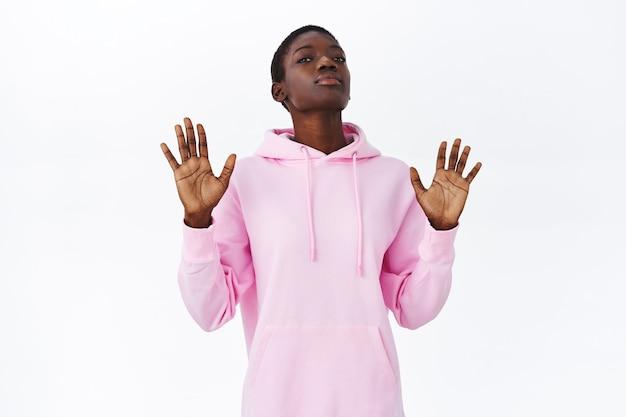 Snobistisch en sceptisch, serieus uitziend afro-amerikaans meisje dat aanbod afwijst, kin opheft en handen vasthoudt in stopgebaar