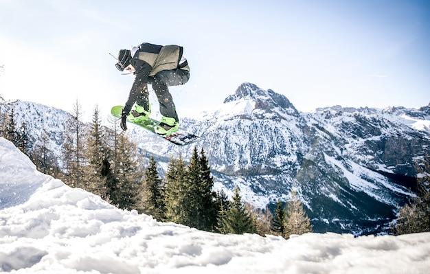 Snoboarder die trucs op de sneeuw uitvoert