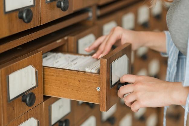 Snoei jonge vrouw kijkend binnen bibliotheeklade