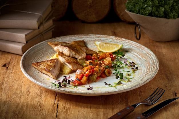 Snoekbaars visfilet en aardappelpuree, schotel op een plaat op een houten tafel.