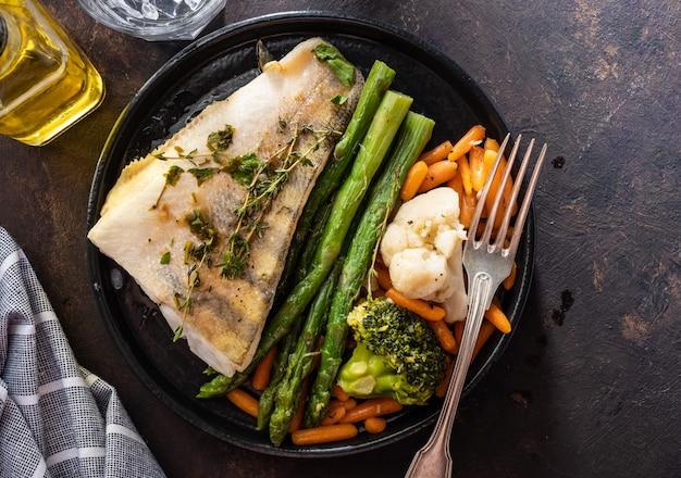 Snoekbaarsfilet met asperges, broccoli en worteltjes. gebakken vis met gestoofde greens