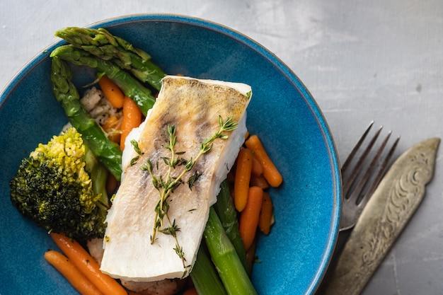 Snoekbaarsfilet met asperges, broccoli en worteltjes. gebakken vis met gestoofde groenten