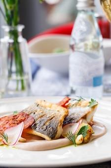 Snoekbaarsfilet met chorizo, bloemkool en radijs in een restaurant serveren. detailopname. keto, paleo, fodmap dieetvoeding.