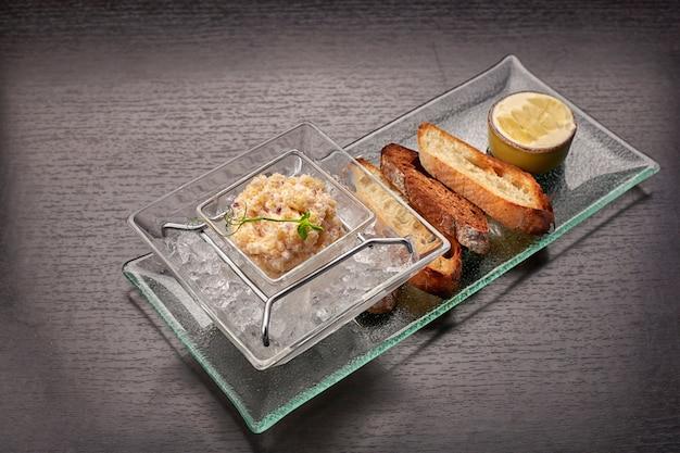 Snoekviskaviaar, op ijs, met croutons en boter, op een doorzichtige schaal, op een donkere achtergrond