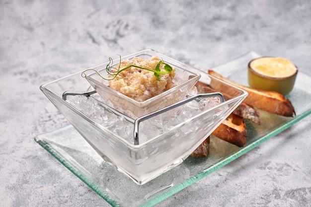Snoekviskaviaar, op ijs, met croutons en boter, op een transparante schaal, op een witte achtergrond