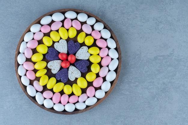 Snoep en koekjes op een rond dienblad, op de marmeren tafel.