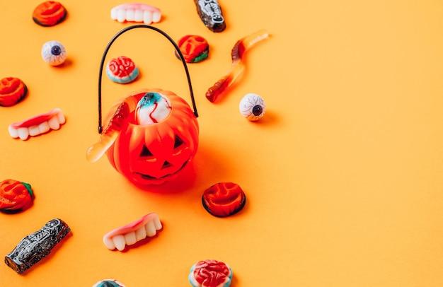 Snoep en lekkernijen voor halloween op oranje achtergrond. selectieve focus met kopieerruimte