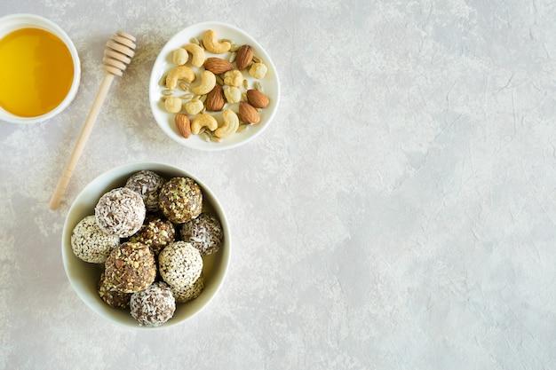 Snoep energie met noten en gedroogd fruit in kom plat lag op grijze achtergrond met kopie ruimte