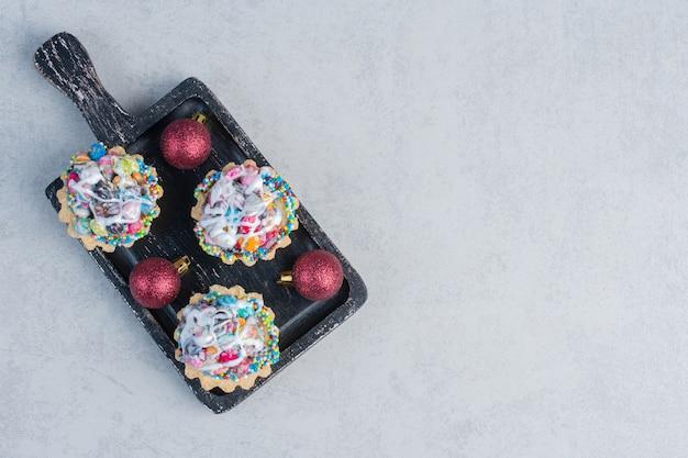 Snoep gegarneerd met cupcakes en kerstballen in een zwarte bak op marmeren oppervlak
