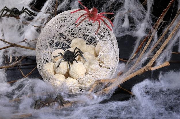 Snoep in de vorm van spinneneieren in een cocon met een spin op tafel voor halloween