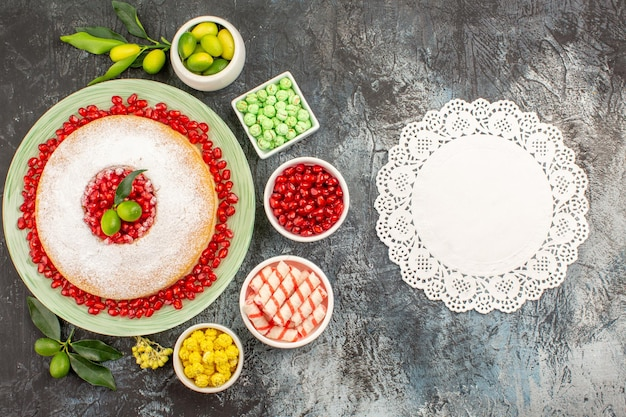 Snoep kant kleedje het bord cake met granaatappel citrusvruchten en snoepjes