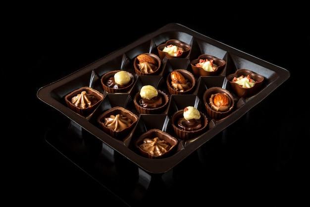 Snoep met room en noten geassorteerde chocolade op geïsoleerde zwarte achtergrond idee voor het dessert in restaurant