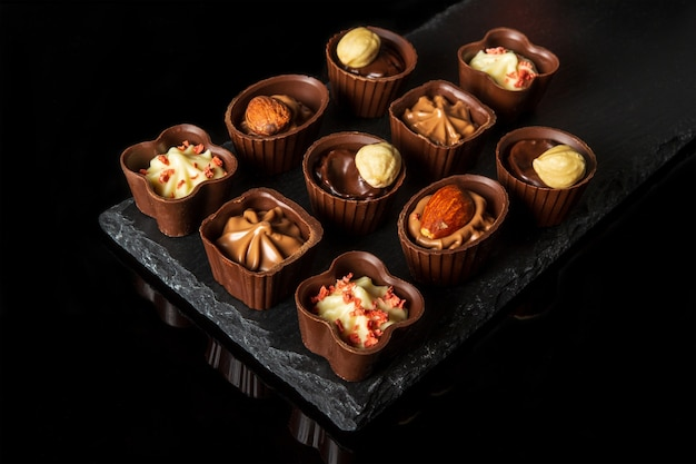 Snoep met room en noten op een leisteen bord geassorteerde chocolade op geïsoleerde zwarte achtergrond idee voor het dessert in een restaurant