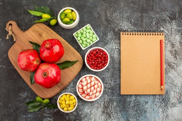 Snoep notitieboekje potlood limoenen granaatappel zaden snoep granaatappels op het bord
