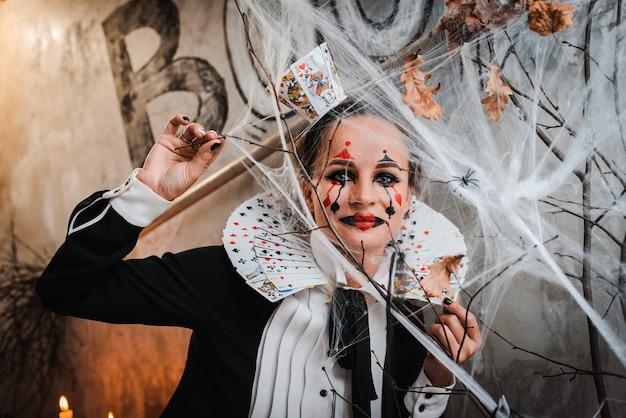Snoep of je leven. portret van een jonge vrouw met griezelige make-up die een queen of hearts-kostuum draagt met een kaartkraag die naar de camera kijkt door het spinnenweb tijdens een bezoek aan het nachtelijke halloween-feest