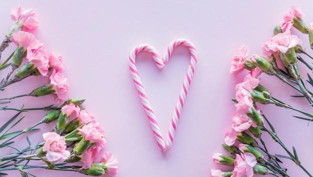 Snoep stokken in hartvorm met bloemen op tafel