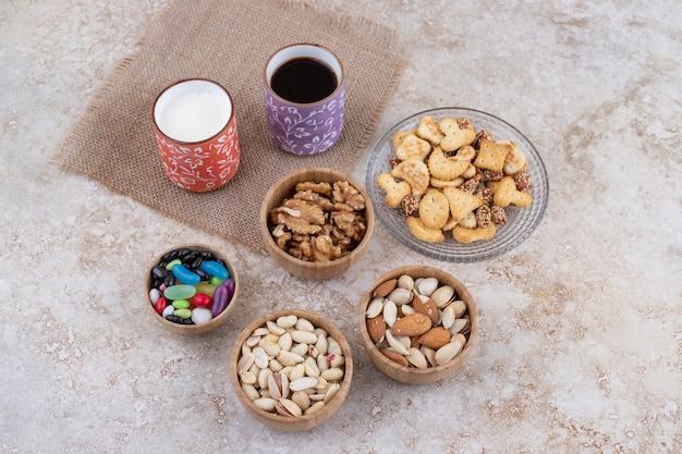 Snoepjes en crackers met kopjes thee en noten