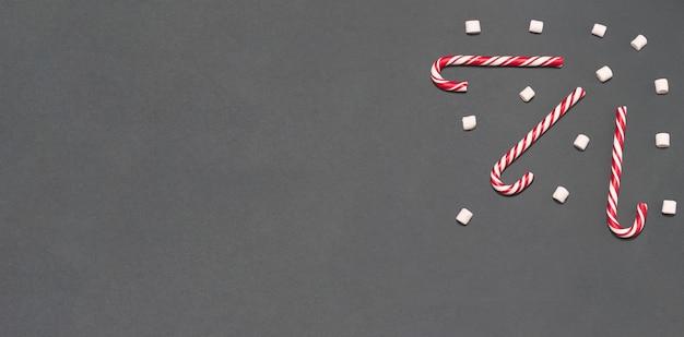Snoepjes en mini marshmallows op grijze achtergrond plat lag bovenaanzicht ruimte kopiëren