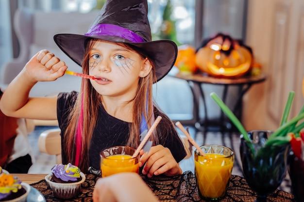 Snoepjes en sap. leuk mooi meisje dat het kostuum van tovenaarshalloween draagt dat van thematische snoepjes en jus d'orange geniet