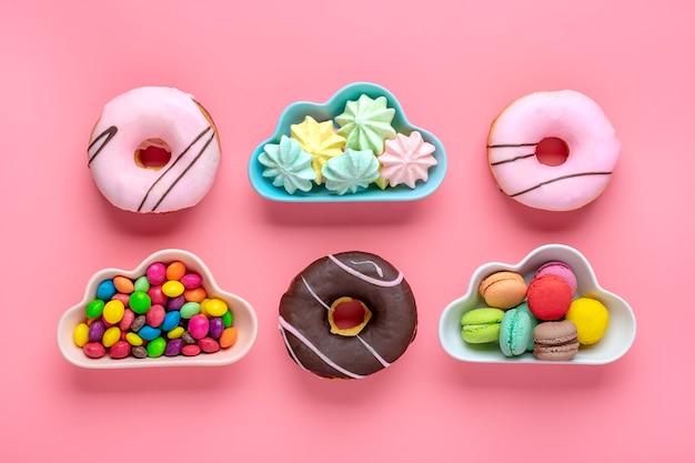 Snoepjes en schuimgebakjes in een kom in de vorm van een wolk, chocolade met kleurrijke topping en roze donut