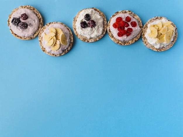 Snoepjes gemaakt van knapperig brood en fruit op een blauw. onderaan is er ruimte voor tekst.