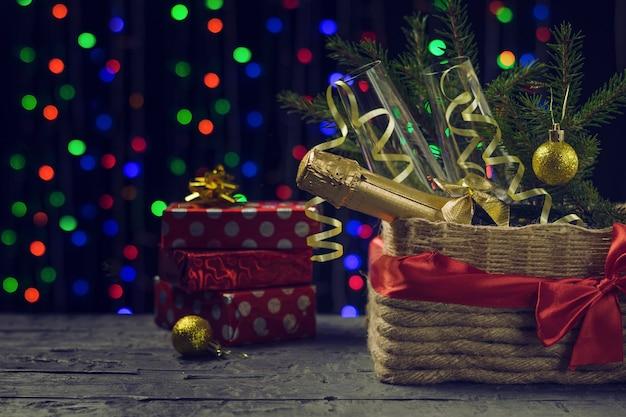 Snoepjes, geschenkdozen en champagne onder een kerstboom. concept van kerstmis en nieuwjaar.