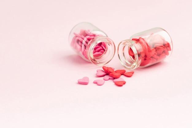 Snoepjes - harten in kleine glazen flesjes. kleurrijke valentijnsdag hartvormige snoep met kopie ruimte. sainte valentine, moederdag wenskaarten, uitnodiging.