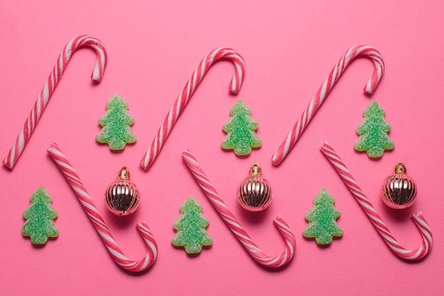 Snoepjes in de vorm van een kerstboom en gouden ballen liggen op een roze achtergrond, bovenaanzicht. kerstmis en nieuwjaar concept