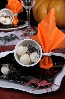 Snoepjes in de vorm van spinneneieren in een kopje op tafel in halloween