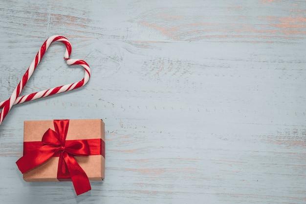 Snoepjes in hartvorm en een ambacht aanwezig met rood lint op een licht geschilderde houten achtergrond. bovenaanzicht, plat liggend. valentijnsdag concept. copyspace.