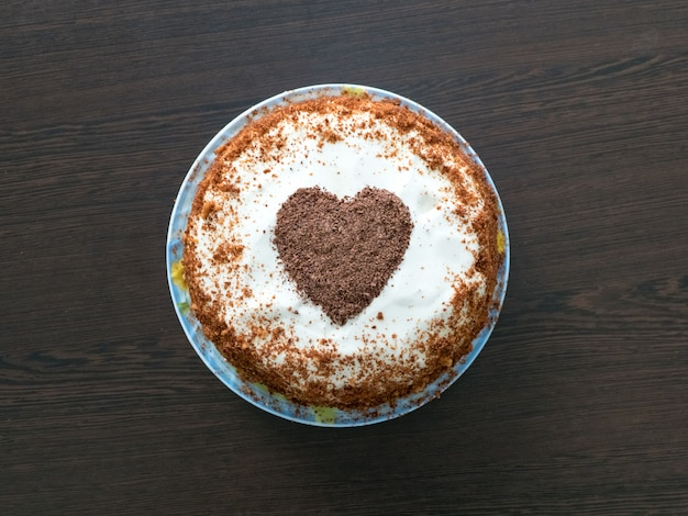 Snoepjes voor valentijnsdag. met de hand gemaakte pastei met roomkaas het berijpen en een chocoladehart. valentijnsdag concept.