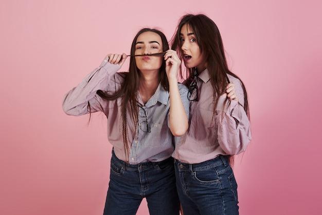Snor maken met haar. jonge vrouwen die pret hebben. schattige tweeling