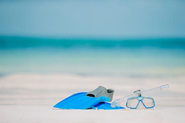 Snorkeluitrusting masker, snorkel en vinnen op wit strand