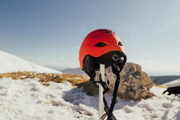 Snowboarden rode helm in de besneeuwde berg met blauwe hemel