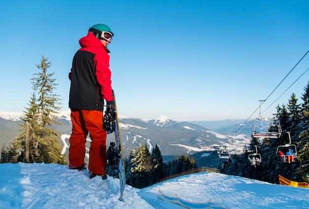 Snowboarder bovenop helling in winteravond