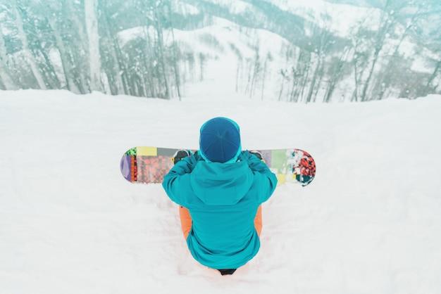 Snowboarder die helling bekijkt