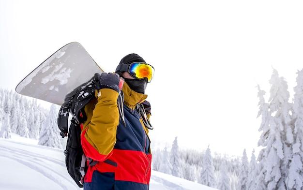 Snowboarder die in beschermende glazen zijn snowboard op zijn rug houdt
