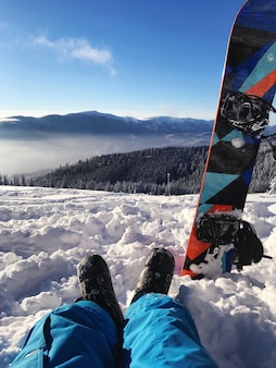 Snowboarder die op a van bergen rust