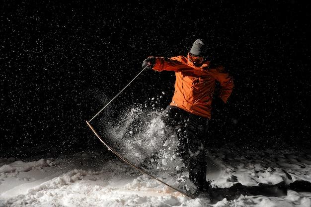 Snowboarder in oranje sportkleding en masker springen op een besneeuwde heuvel 's nachts