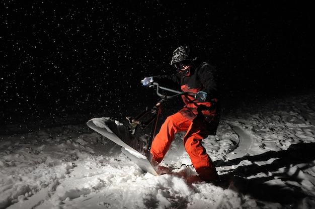 Snowboarder in oranje sportkleding springen op een besneeuwde heuvel 's nachts
