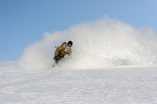 Snowboarder in speciaal pak glijdt over de berg en heft sneeuw achter hem op