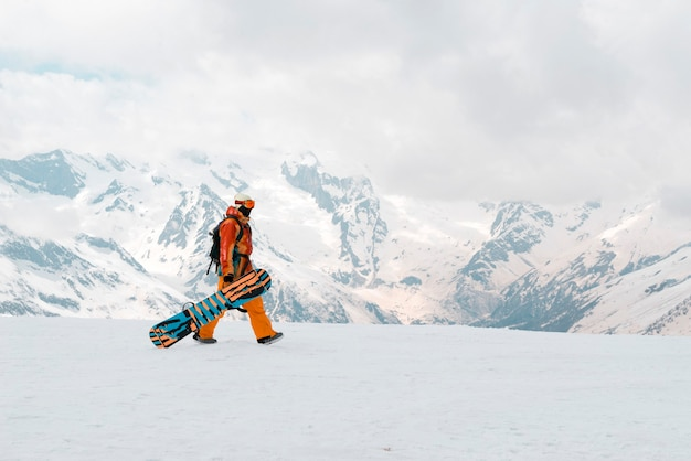 Snowboarder man met een snowboard in de hand is in de sneeuw in de bergen