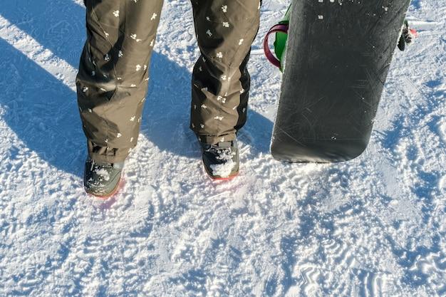 Snowboarder met snowboard staan op skipiste in de winter