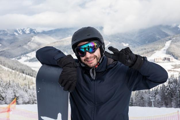 Snowboarder met snowboardportret met overwinningsteken op de bovenkant van bergenheuvel vóór rit