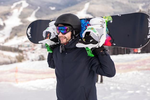 Snowboarder ontspannen en poseren op zonnige dag op ske resort met snowboard boven het hoofd. wintertijd.