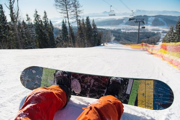 Snowboarder oogpunt op zijn voeten op de besneeuwde helling onder skilift op zonnige dag in de bergen