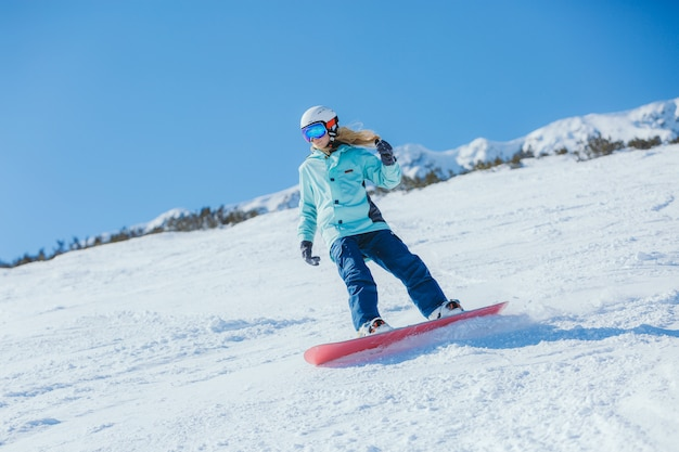 Snowboarder op de hellingen op een zonnige ochtend. meisje in snowboarderkleren.