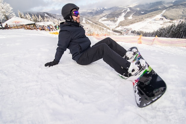 Snowboarder op de heuvelknopen die vóór rit op sneeuwheuvel vastmaken