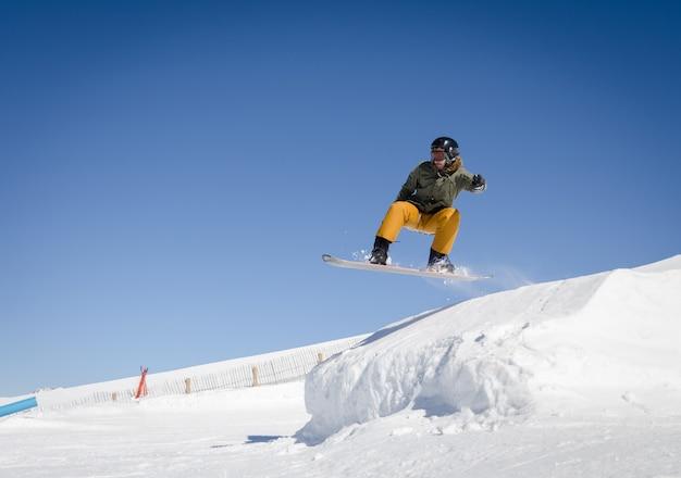 Snowboarder springen met een blauwe en zonnige hemel in zermatt, de zwitserse alpen