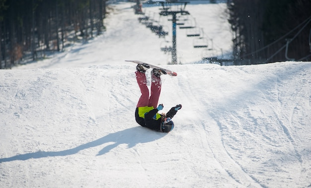 Snowboarder valt op de hellingen tijdens de afdaling